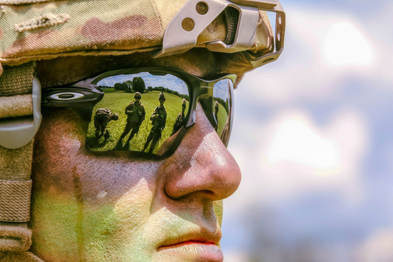 Troops on green grass are reflected in the sunglasses of a soldier staring ahead.