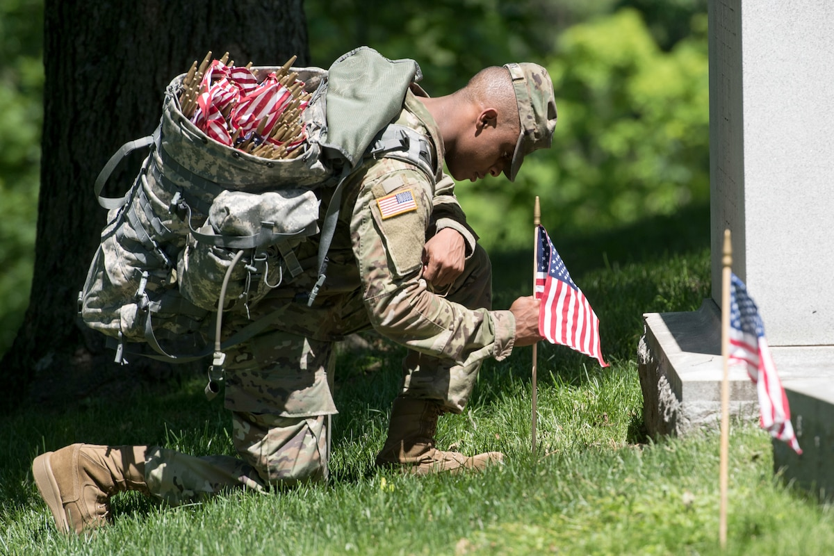 A soldier kneels at a grave to place a flag.