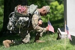 Soldier places a flag on a grave in Arlington National Cemetery.