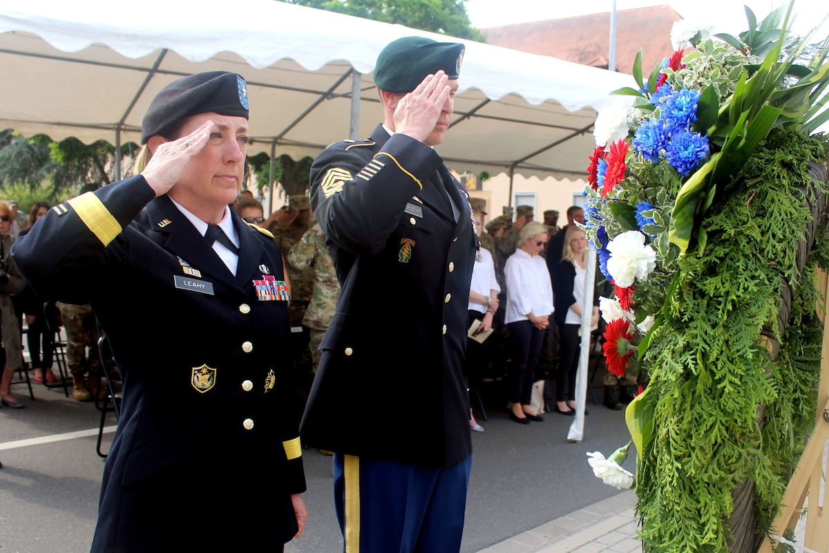 Two soldiers salute a wreath.
