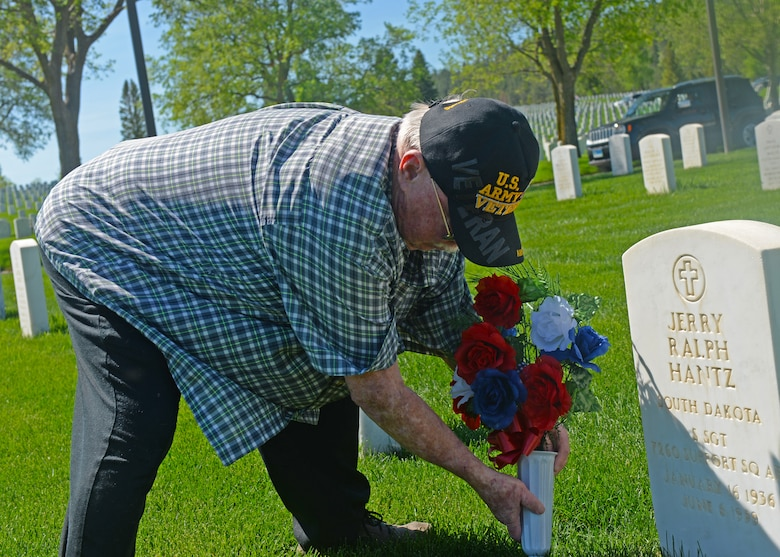 Jack Kantz sets flowers at his brother's grave during Memorial Day weekend at the Black Hills National Cemetery near Sturgis, S.D., May 26, 2018.  Whenever a service member is interned at a cemetery, the ceremony can conclude with a seven-volley salute, followed by the sound of taps. (U.S. Air Force photo by Airman 1st Class Nicolas Z. Erwin)