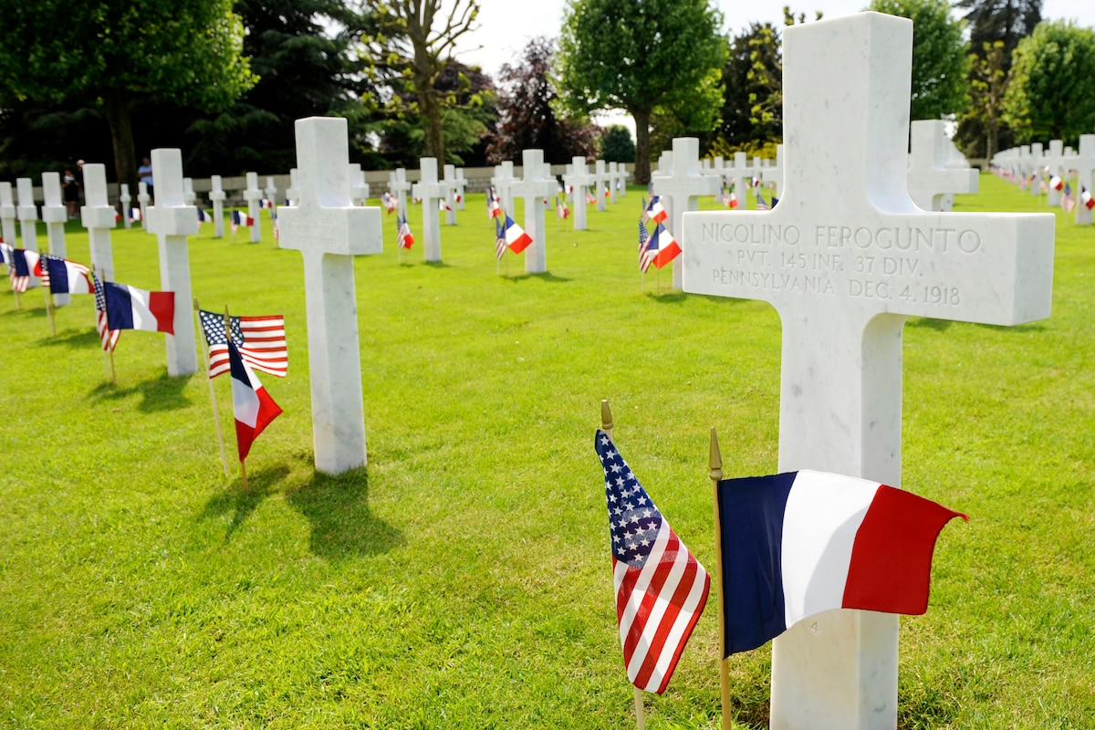 Rows of crosses have American and French flags in front of them.