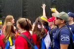 A group of 13 to 15 year olds attending the Tragedy Assistance Program for Survivor's 24th annual National Military Survivor Seminar and Good Grief Camp, along with their mentors, point to the name of Air Force Col. Charles Stoddard Rowley, father of mentor Patti Rowley, at the Vietnam Veterans Memorial wall in Washington.