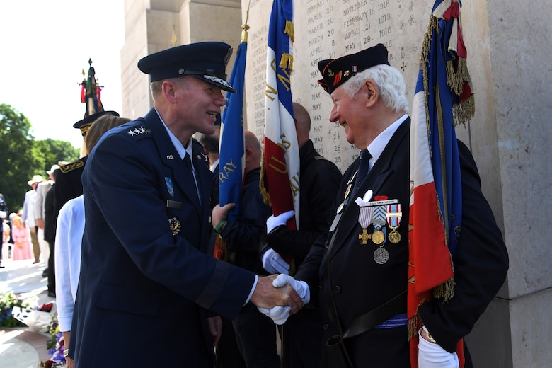 Gen. Wolters shakes hands with a flag bearer at Lafayette Escadrille Memorial.