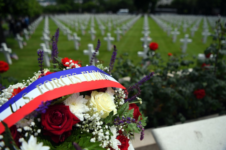 A flower wreath lays on a bench with the Suresnes American Cemetery in the background.