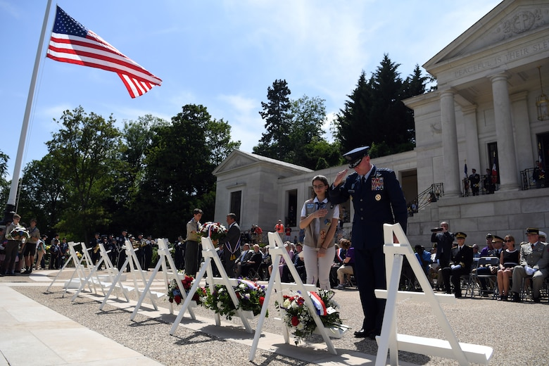 Gen. Wolters and girl scout salute the memorial wreath during memorial day ceremony at Suresnes American Cemetery.