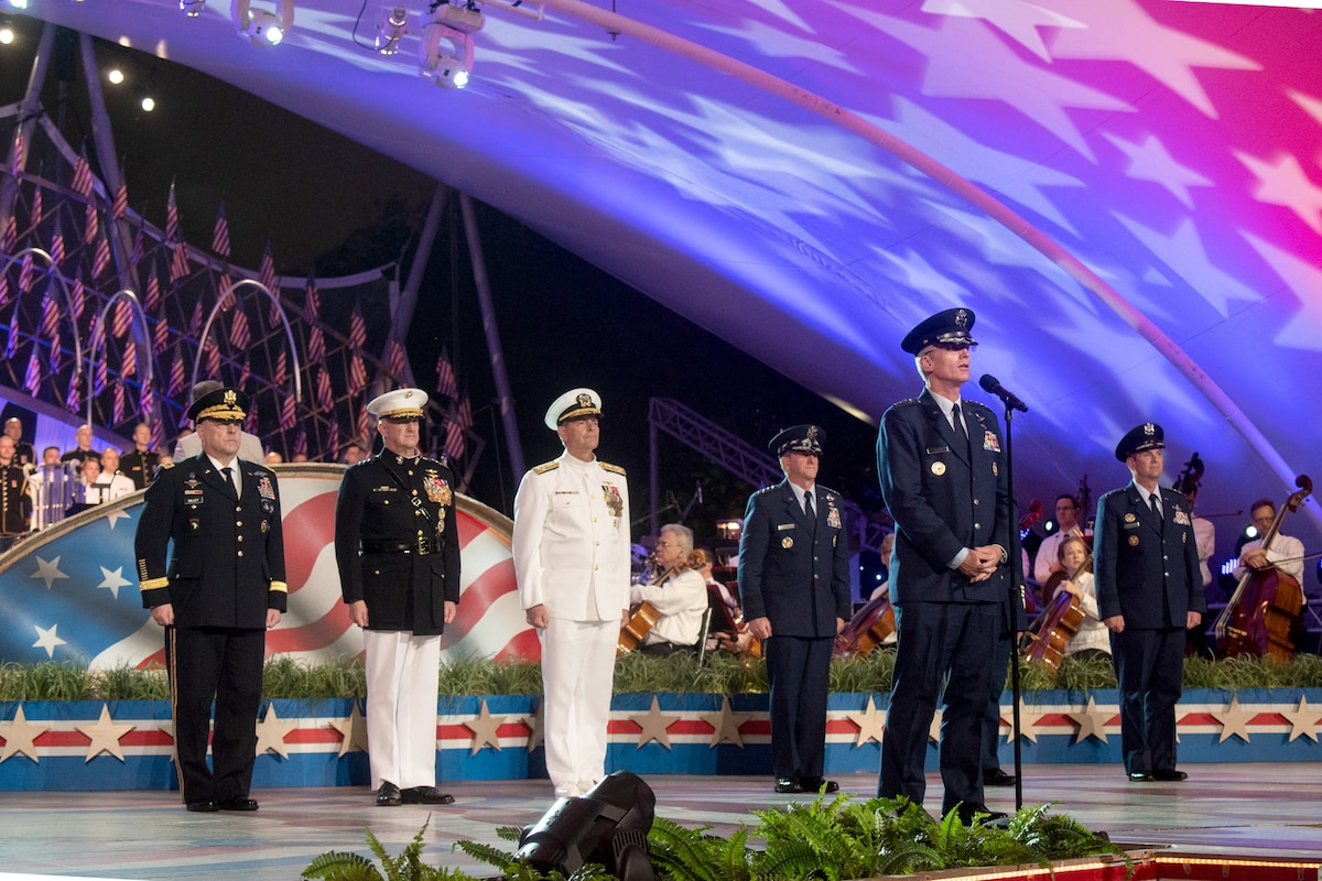 Military officers stand on a stage with the vice chairman of the Joint Chiefs of Staff.