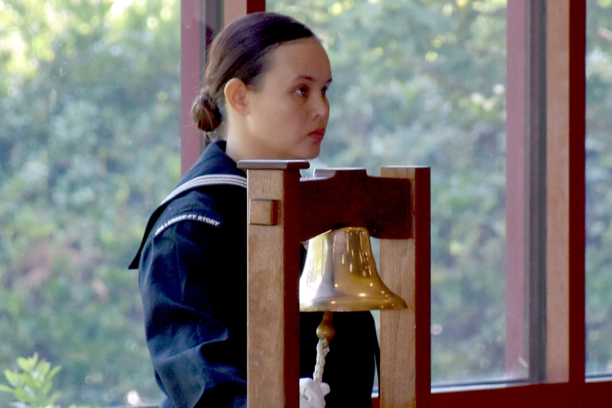 A sailor rings a bell.