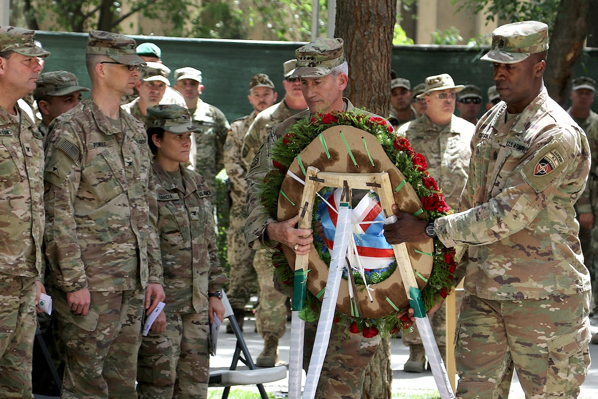 Two soldiers carry a wreath.