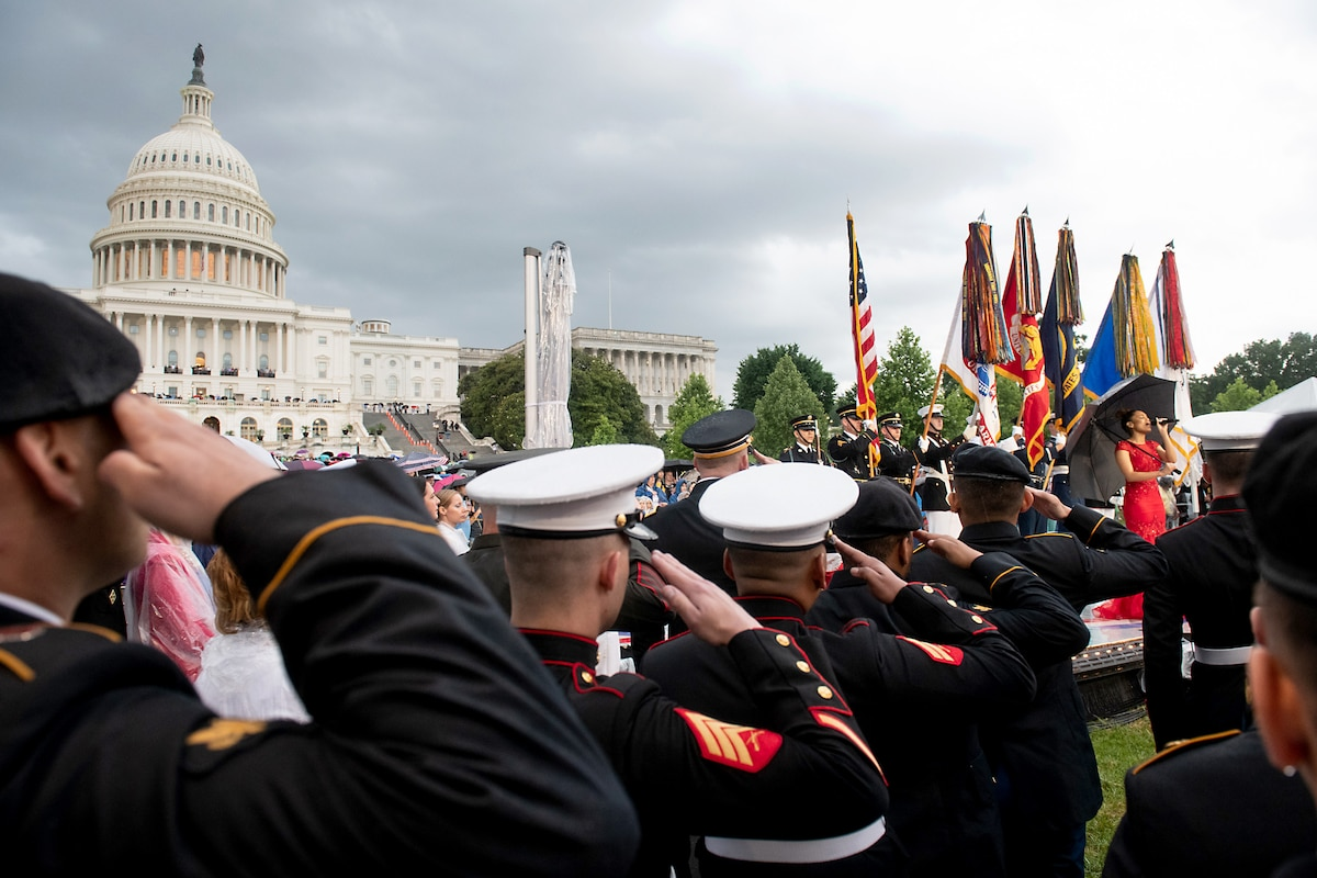 A woman on a stage sings in front of the Capitol building while service members salute.