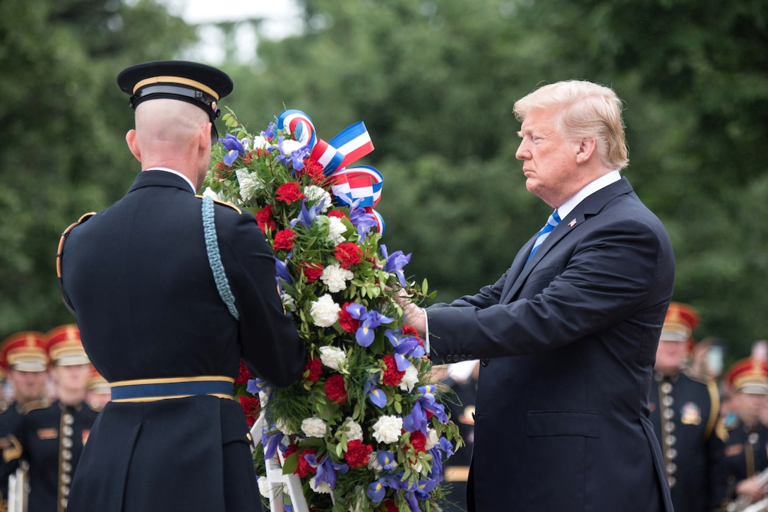 The president places a wreath with the help of a soldier.