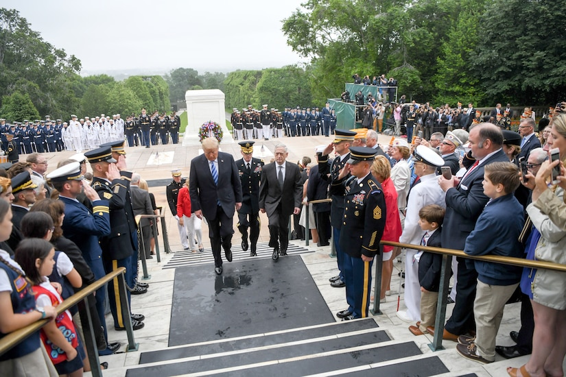 The president, defense secretary and others walk up steps.