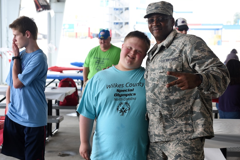 U.S. Air Force Tech. Sgt. Aldrich Cherry, information management with the 145th Maintenance Squadron, poses with athletes at the Z-Max Pavilion, Charlotte N.C., during the annual Special Olympics Day at the Races, May 24, 2018. The Special Olympics Day at the Races is an annual celebration held at the Lowes Motor Speedway and is put on by Vangie Boswell and fourteen sponsors including the North Carolina Air National Guard (NCANG). Members of the NCANG help set-up the event and pass out mementos while mingling with State Special Olympians and their families.(U.S. Air Force photo by Staff Sgt. Laura J. Montgomery/Released)