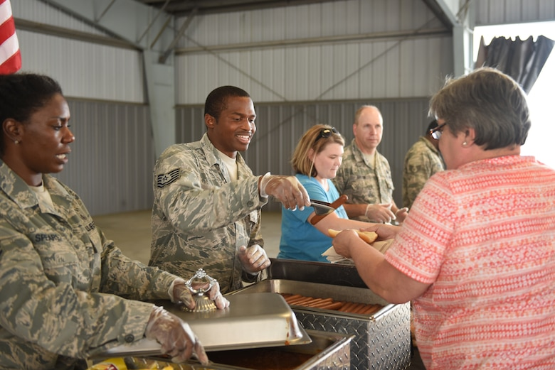 U.S. Air Force Tech. Sgts. Tah-Tah-Nisha Spears (far left), aerospace medical technician with the 145th Medical Group, and Eviat Hayes (center), avionics technician for the 145th Maintenance Squadron, serve food to participants and their families at the Z-Max Pavilion, Charlotte N.C., during the annual Special Olympics Day at the Races, May 24, 2018. The Special Olympics Day at the Races is an annual celebration held at the Lowes Motor Speedway and is put on by Vangie Boswell and fourteen sponsors including the North Carolina Air National Guard (NCANG). Members of the NCANG help set-up the event and pass out mementos while mingling with State Special Olympians and their families.(U.S. Air Force photo by Staff Sgt. Laura J. Montgomery/Released)