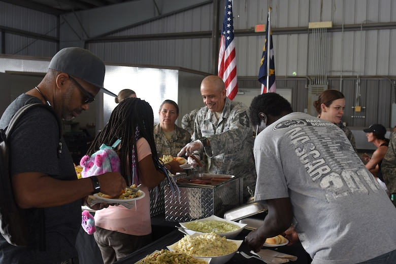 North Carolina National Guard State Command Chief Master Sgt. David Rodriguez (center), serves food to participants and their families at the Z-Max Pavilion, Charlotte N.C., during the annual Special Olympics Day at the Races, May 24, 2018. The Special Olympics Day at the Races is an annual celebration held at the Lowes Motor Speedway and is put on by Vangie Boswell and fourteen sponsors including the NCANG. Members of the NCANG help set-up the event and pass out mementos while mingling with State Special Olympians and their families.(U.S. Air Force photo by Staff Sgt. Laura J. Montgomery/Released)