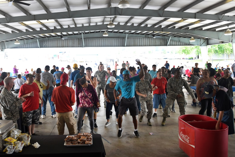 Members of the North Carolina Air National Guard, athletes, and their family members join in a dance at the Z-Max Pavilion, Charlotte N.C., during the annual Special Olympics Day at the Races, May 24, 2018. The Special Olympics Day at the Races is an annual celebration held at the Lowes Motor Speedway and is put on by Vangie Boswell and fourteen sponsors including the North Carolina Air National Guard (NCANG). Members of the NCANG help set-up the event and pass out mementos while mingling with State Special Olympians and their families.(U.S. Air Force photo by Staff Sgt. Laura J. Montgomery/Released)