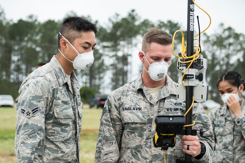 U.S. Airmen assigned to the 20th Civil Engineer Squadron mark the coordinates of a found object during a search and recovery exercise at Shaw Air Force Base, S.C., May 23, 2018.