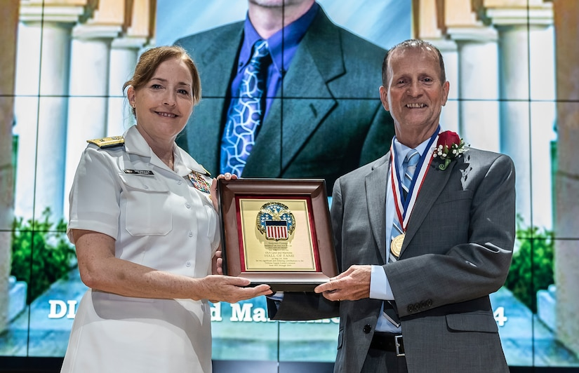Finney receives a plaque and medal from Defense Logistics Agency Land and Maritime Commander Navy Rear Adm. Michelle Skubic