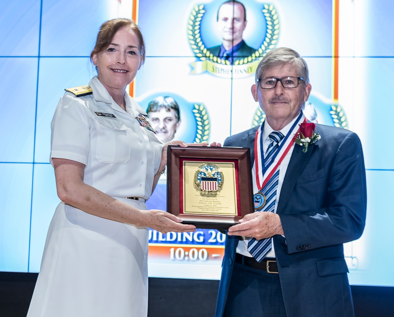 Stephen E. Rodocker receives a plaque and medal from Defense Logistics Agency Land and Maritime Commander Navy Rear Adm. Michelle Skubic