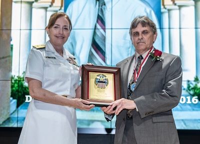 Harvey P. Hodak receives a plaque and medal from Defense Logistics Agency Land and Maritime Commander Navy Rear Adm. Michelle Skubic.
