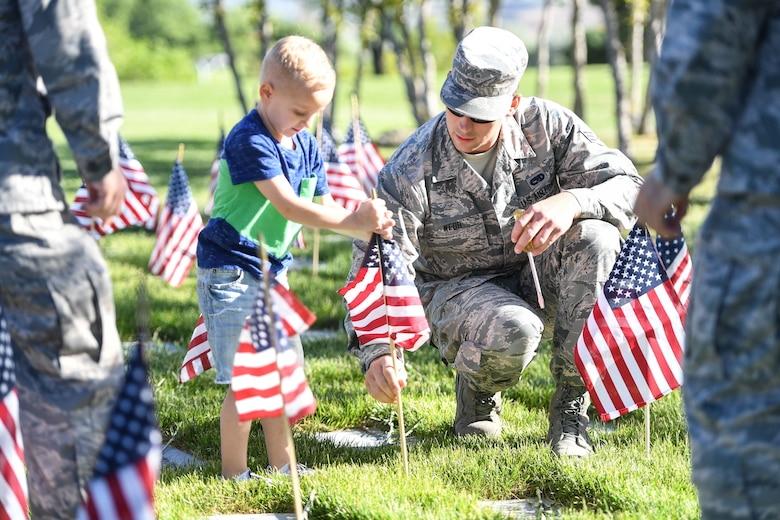 Senior Airman James Webb, 388th Maintenance Squadron, places a flag with Jaxton Gardner, son of Master Sergeant Phillip Gardner, 729th Air Control Squadron, May 26, 2018, at the Veterans Memorial Cemetery at Camp Williams, Utah. Several Airmen from Hill Air Force Base participated in the annual flag laying event over Memorial Day weekend. (U.S. Air Force photo by Cynthia Griggs)
