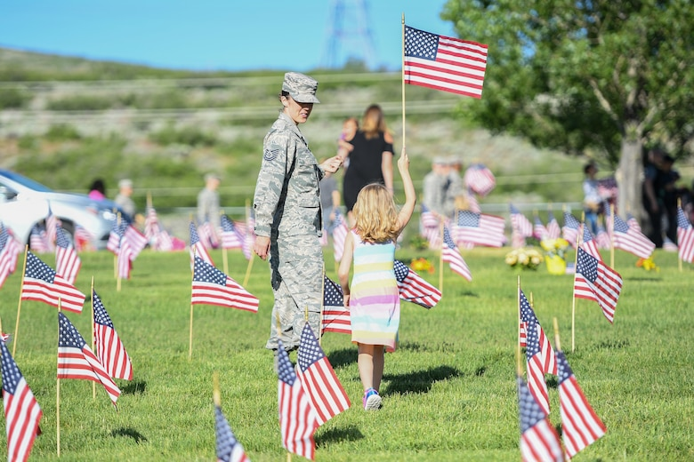 Tech. Sgt. Adrian Villa, 419th Fighter Wing, places a flag with her daughter, Presley Wigman, May 26, 2018, at the Veterans Memorial Cemetery at Camp Williams, Utah. Several Airmen from Hill Air Force Base participated in the annual flag laying event over Memorial Day weekend. (U.S. Air Force photo by Cynthia Griggs)