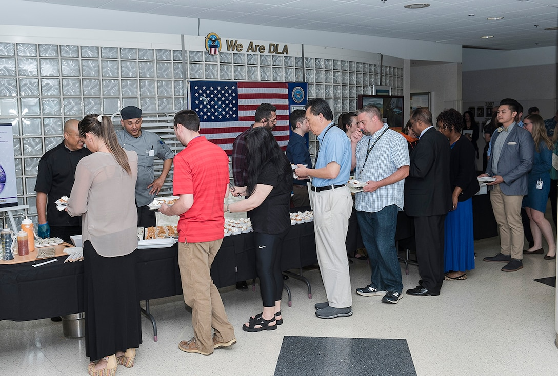 Members of the Central Ohio Defense Federal Community prepare to sample foods during the Asian American Pacific Islander Month