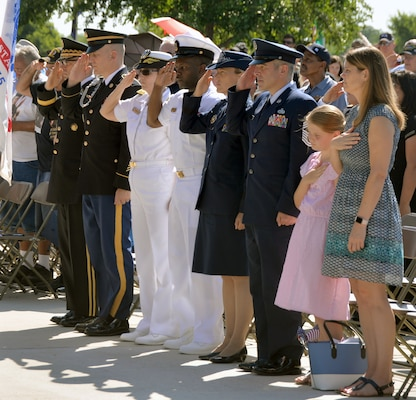 Local Joint Base San Antonio military leaders salute the colors, presented by members of the Southside High School Junior Air Force ROTC Honor Guard, during the Memorial Day ceremony at the Fort Sam Houston National Cemetery amphitheater May 28.