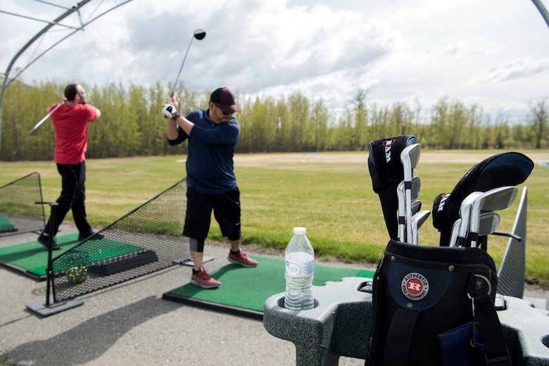 Sean Fields and Rommel Reyes practice their golf swings at Moose Run Golf Course driving range at Joint Base Elmendorf-Richardson, Alaska, May 21, 2018. Both Fields and Reyes have been using the course for more than a year and have experienced the relaxed environment and tournaments it has to offer.
