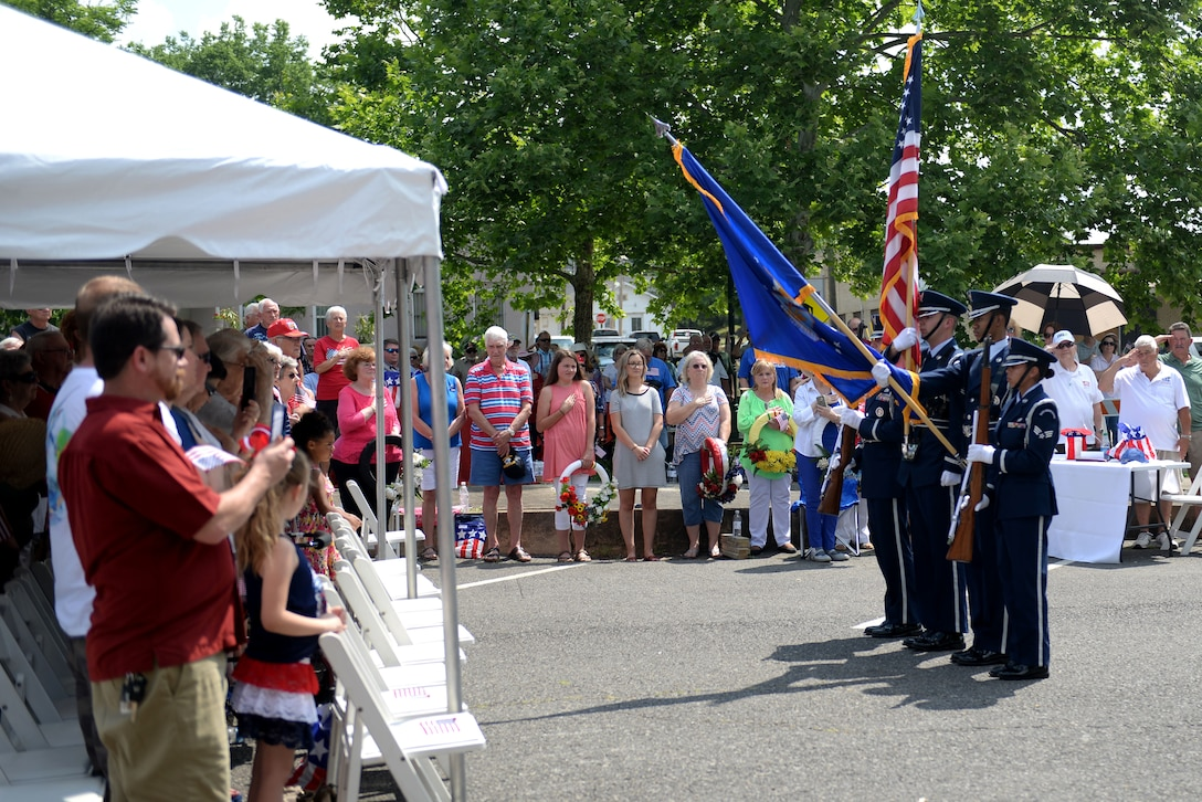Four honor guardsmen present the colors to a crowd.
