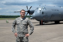 A man in the Airman Battle Uniform stands with his hands on his hips in front of a C-130J.