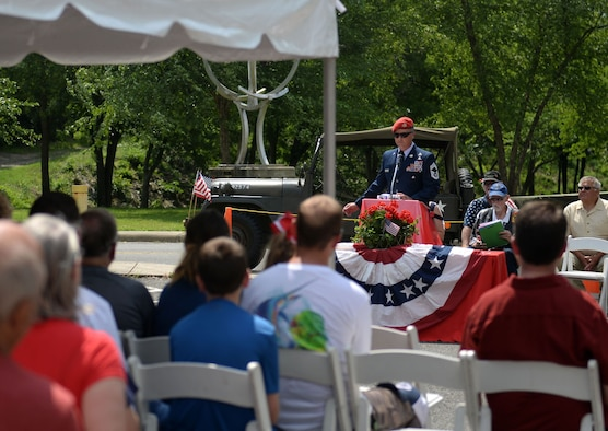 A man in the Air Force service dress uniform and a red beret speaks to a crowd.