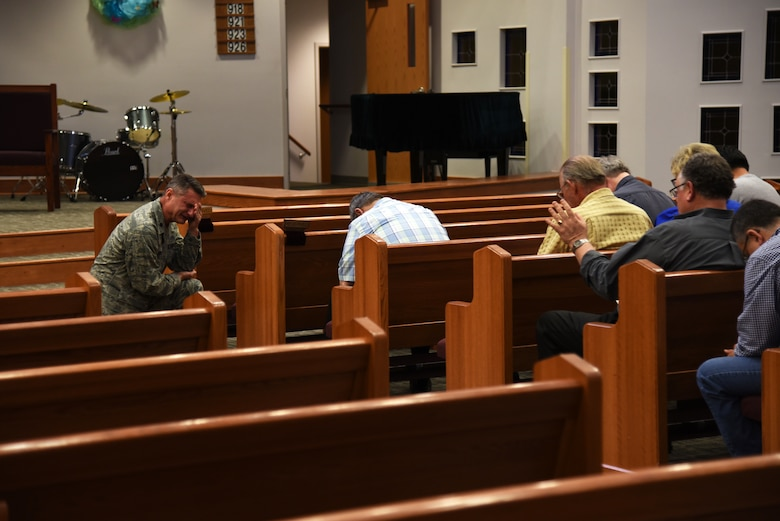 U.S. Air Force Lt. Col. Robert Borger, 17th Training Wing chaplain, kneels for an open prayer session during Clergy Day at the Taylor Chapel on Goodfellow Air Force Base, Texas, May 24, 2018. Borger gathered 25 local pastors to teach them about Goodfellow, its mission and its service members. (U.S. Air Force photo by Staff Sgt. Joshua Edwards/Released)