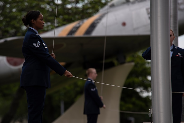 U.S. Air Force Staff Sgt. Jalessa Randle, the 35th Force Support Squadron commander executive assistant, lowers the American flag during a Memorial Day ceremony at Misawa Air Base, Japan, May 25, 2018. Six Airmen with the 35th Fighter Wing served as ceremonial caretakers of the U.S. and Japan flags during the ceremony. (U.S. Air Force photo by Airman 1st Class Collette Brooks)