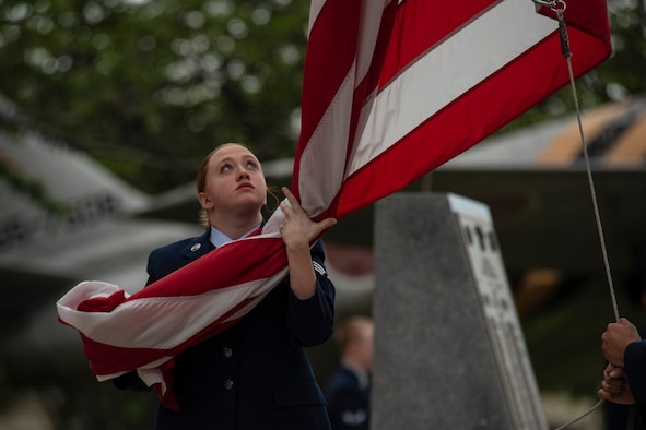 U.S. Air Force Senior Airman Sarah Rose, a 35th Maintenance Squadron electrical and environmental apprentice, holds the American Flag during a Memorial Day ceremony held at Misawa Air Base, Japan, May 25, 2018. It is customary for the flag to be lowered during the ceremony to remember and pay respect to fallen service members. (U.S. Air Force photo by Airman 1st Class Collette Brooks)