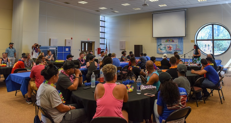 """Airmen listen to opening remarks from Tech. Sgt. Margaret Asuega during the """"Taste of Asia and Pacific"""" event."""