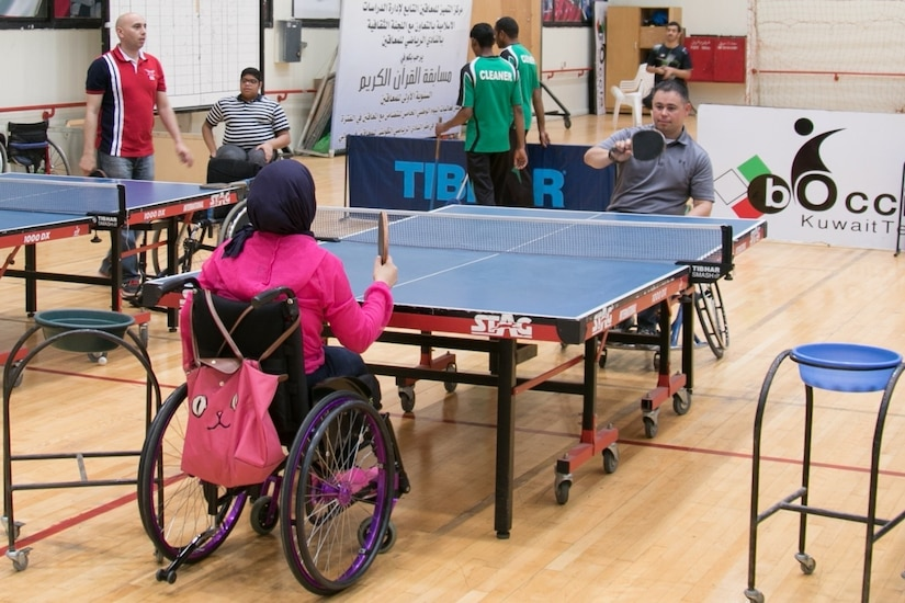 """Capt. Nick P. Branoff, an aeromedical evacuation officer for the 28th Infantry Division, Task Force Spartan volleys the ping pong ball back across the table against a member of the Kuwait Disabled Sports Club in a game of table tennis. More than 50 Task Force Spartan Soldiers participated alongside their Kuwaiti neighbors in sporting competitions at the Kuwait Disabled Sports Club, May 9. The Soldiers had the opportunity to compete in wheelchair sporting competitions such as basketball, fencing, table tennis, and bocce. Continuing the legacy of  """"Every Soldier is an Ambassador,"""" a program to encourage interactions between Americans and Kuwaitis, Soldiers of the 28 ID were among a combined group of more than 100 Kuwait and U.S. Army athletes participating in sporting events held at Kuwait Disabled Sports Club."""