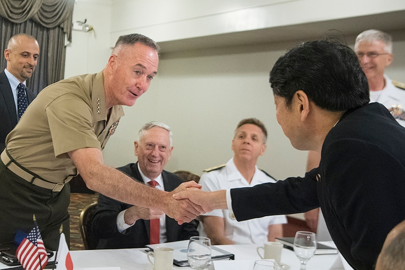 Two men shake hands over a table.