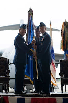 Lt. Gen. Giovanni Tuck, 18th Air Force commander, left, passes the 62nd Airlift Wing guidon to Col. Scovill Currin, 62nd Airlift Wing incoming commander, during a change of command ceremony May 24, 2018, at Joint Base Lewis-McChord, Wash. Currin comes to JBLM from his previous assignment as the commander of the 916th Air Refueling Wing. (U.S. Air Force photo by A1C Sara Hoerichs)