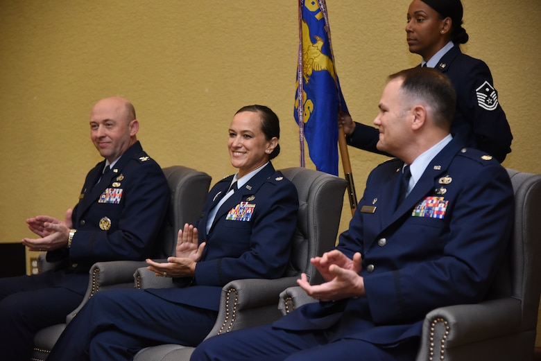 U.S. Air Force Col. Danny Davis, 81st Mission Support Group commander, Lt. Col. Melissa Rativa, 81st Logistics Readiness Squadron outgoing commander, and Maj. Matthew Roberts, incoming 81st LRS commander, applaud during the 81st LRS change of command ceremony in the Bay Breeze Event Center at Keesler Air Force Base, Mississippi, May 23, 2018. The ceremony is a symbol of command being exchanged from one commander to the next by the hand off of a ceremonial guidon. Davis passed on command of the 81st LRS to Roberts. (U.S. Air Force photo by Kemberly Groue)