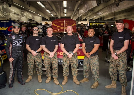 U.S. Marines with 6th Marine Corps District pose for a group photo with Spencer Boyd, the driver of the Grunt Style stock car, during the Coca-Cola 600 at the Charlotte Motor Speedway on May 24, 2018. The Marines took part in the battles won challenge trailer at the Coca-Cola 600 NASCAR race to spread awareness of the opportunities that the Marine Corps can provide. (U.S. Marine Corps photo by Lance Cpl. Jack A. E. Rigsby)