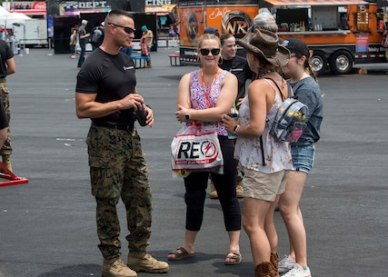Major Jason G. Ellis, Commanding Officer of Recruiting Station Columbia, speaks to attendants of the Coca-Cola 600 at the Charlotte Motor Speedway on May 26, 2018. The Marines took part in the battles won challenge trailer at the Coca-Cola 600 NASCAR race to spread awareness of the opportunities that the Marine Corps can provide. (U.S. Marine Corps photo by Lance Cpl. Jack A. E. Rigsby)