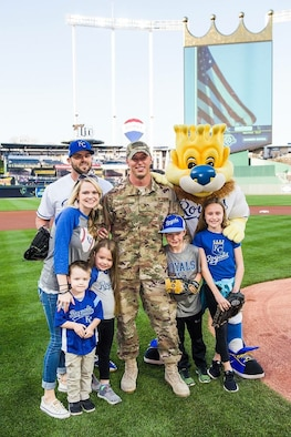 U.S. Air Force Tech. Sgt. Sean Laffey, armament specialist, assigned to the 442d Maintenance Squadron, holds his daughter as his family runs to welcome him home at Kauffman Stadium, Kansas City, Mo., May 19, 2018.