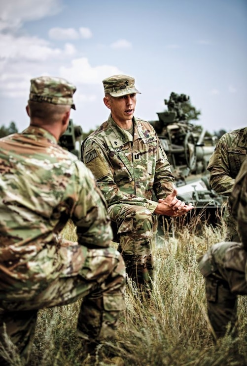 Caucasian male Chaplain CPT Stene kneeling whle delivering a sermon to group of Soldiers wearing OCP outside during the day.