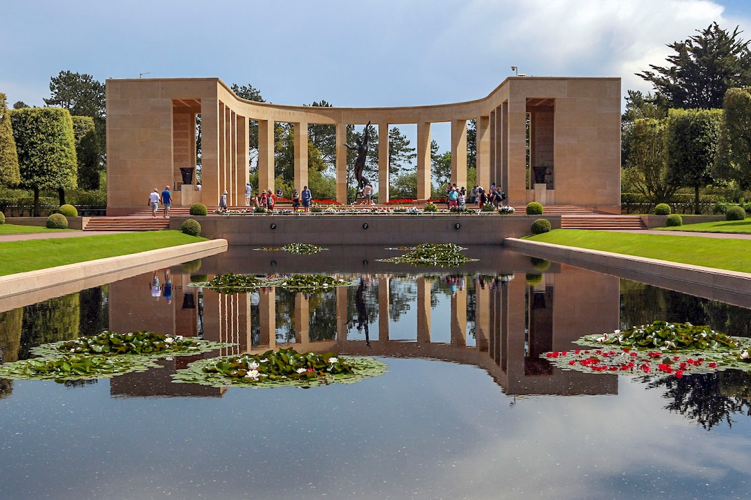 A reflecting pool shows the image of a memorial structure standing behind it.