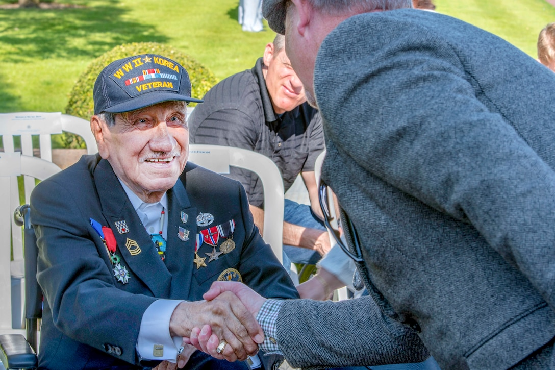 A World War II veteran wearing medals on his blazer shakes hands with someone with sitting at an outdoor ceremony.