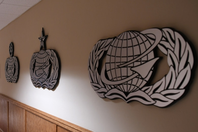 Personnel occupational badges are displayed in the Personnel Apprentice Course hallway in Wolfe Hall at Keesler Air Force Base, Mississippi, May 24, 2018. The hallway underwent a five-month renovation, which was envisioned by U.S. Air Force Master Sgt. Glenn Davis, previous PAC instructor, to inspire PAC students that walk along through hall. (U.S. Air Force photo by Airman 1st Class Suzie Plotnikov)