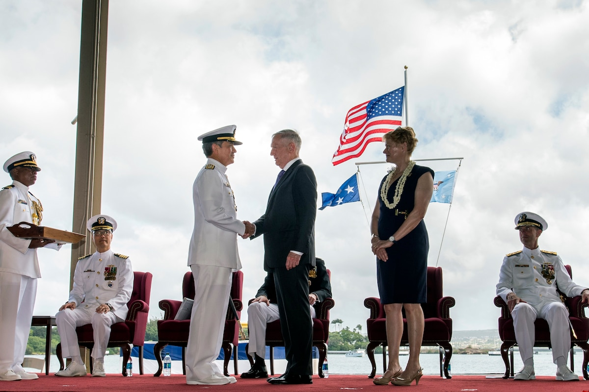 Defense Secretary James N. Mattis shakes hands with Navy Adm. Harry B. Harris Jr. on stage.