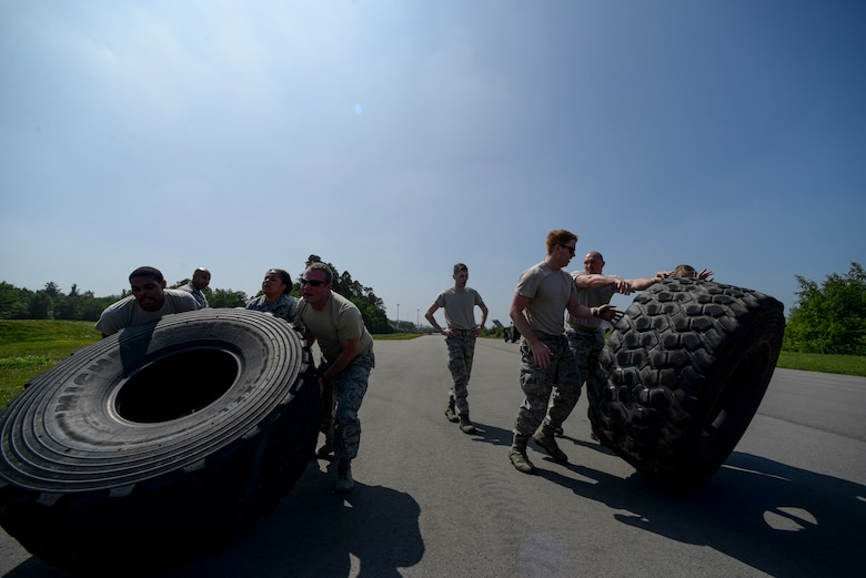 Atlantic Stripe Conference participants flip tires during an obstacle course on Ramstein Air Base, Germany, May 18, 2018. The professional development conference allowed noncommissioned officers time away from official duties to learn from leaders, mentors and guest speakers. (U.S. Air Force photo by Airman 1st Class D. Blake Browning)