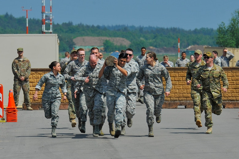 Atlantic Stripe Conference participants perform a log carry as part of an obstacle course on Ramstein Air Base, Germany, May 18, 2018. The Airmen were selected to attend the conference due to their potential to serve in higher leadership positions as they continue throughout their careers. (U.S. Air Force photo by Airman 1st Class D. Blake Browning)